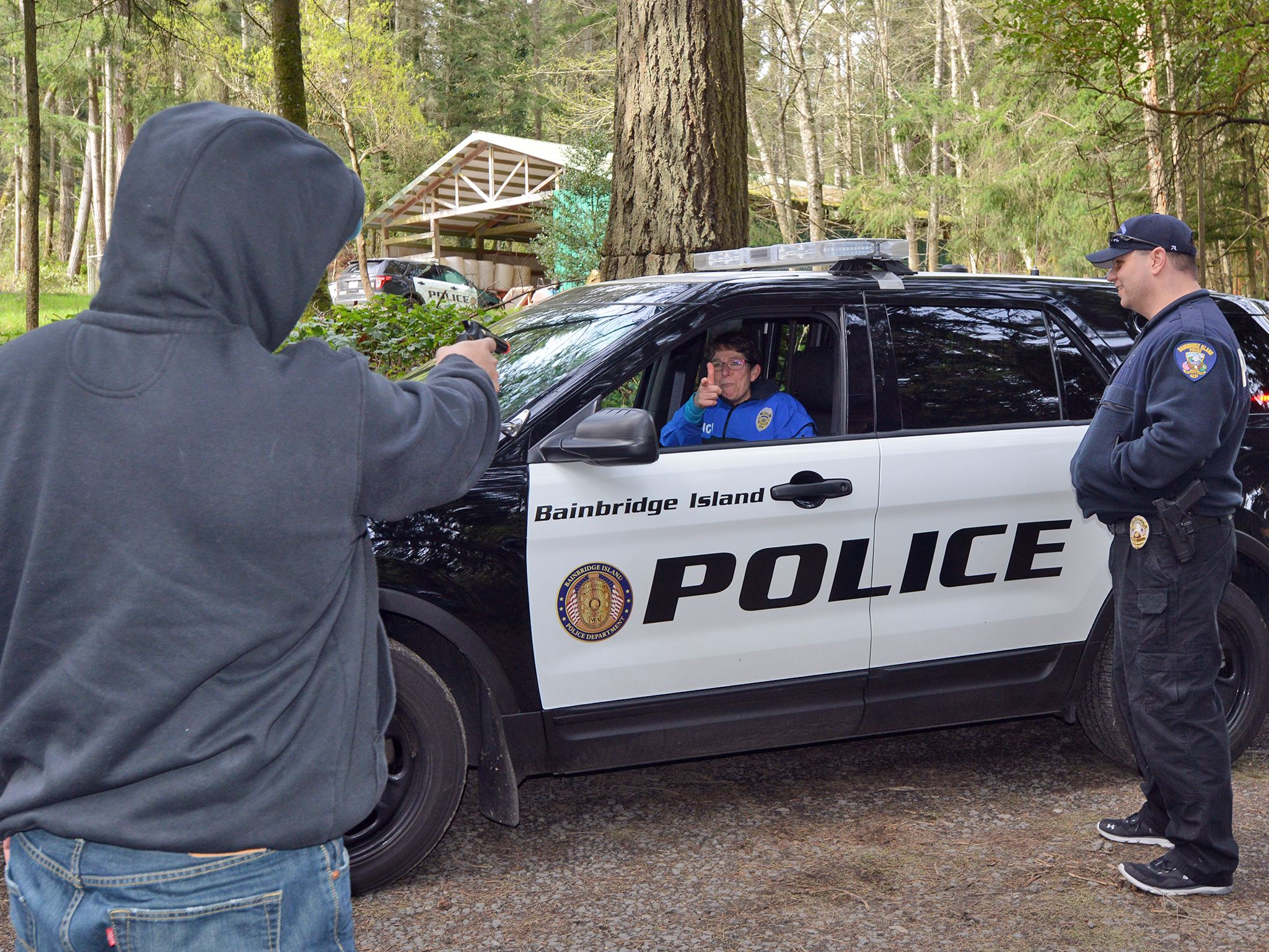 Mock standoff between hooded figure with toy gun and woman in a Police SUV.